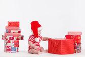 Adorable niño con gorra de santa con pilas de cajas presentes alrededor de — Foto de Stock