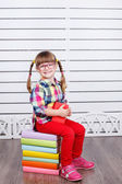Little girl sitting on stack of books — Stock Photo