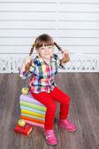 Bambina seduta su una pila di libri — Foto Stock