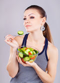 Close-up of pretty girl eating fresh vegetable salad — Stock Photo