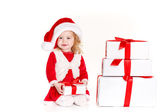 Child holding present wearing santa hat isolated on white — Stock Photo