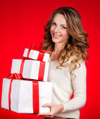 Woman wrapping christmas presents wearing santa hat. — Stock Photo