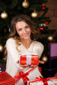 Girl near the Christmas tree with gifts — Stock Photo