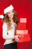 Attractive girl in Santa hat with gifts isolated on red — Stock Photo