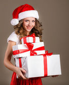Girl in santa claus hat holding gifts. — Stock Photo
