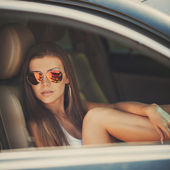 Portrait of beautiful sexy fashion woman model with bright makeup sitting in a car — Stock Photo
