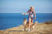 Mladá žena, pes labrador, moře — Stock fotografie
