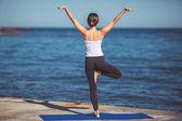 Młoda kobieta, brzeg morza, ćwiczenia jogi — Zdjęcie stockowe