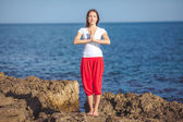 молодая женщина, берег моря, упражнения йоги — Стоковое фото