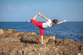 Young woman, sea shore, yoga exercises — Stock Photo