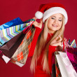 Beautiful blonde dressed as Santa with a gift in her hands, isolated on red — Stock Photo #37100795