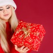Beautiful blonde dressed as Santa with a gift in her hands, isolated on red — Stock Photo #37100801