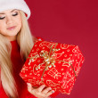 Beautiful blonde dressed as Santa with a gift in her hands, isolated on red — Stock Photo