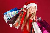 Piękna blondynka w stroju świętego mikołaja prezentu w jej ręce, na czerwonym tle — Zdjęcie stockowe
