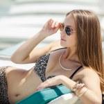 Woman sunbathing in bikini at tropical travel resort. Beautiful young woman lying on sun lounger near pool — Stock Photo #37178145