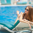 Woman sunbathing in bikini at tropical travel resort. Beautiful young woman lying on sun lounger near pool — Stockfoto