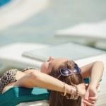 Woman sunbathing in bikini at tropical travel resort. Beautiful young woman lying on sun lounger near pool — Stock Photo #37178181