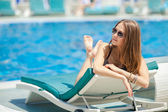 Woman sunbathing in bikini at tropical travel resort. Beautiful young woman lying on sun lounger near pool — Stock Photo