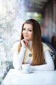 Hezká mladá žena sedí v kavárně s šálkem kávy — Stock fotografie