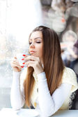 Pretty young woman sitting in the cafe with a cup of coffee — Stock Photo