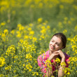 Young beautiful woman in flowering field in summer. Outdoors — Stock Photo