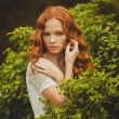 Portrait of young beautiful redhair woman standing in green summer park — Stock Photo
