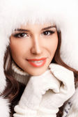 Winter portrait of beautiful smiling woman with snowflakes in white furs — Stock Photo