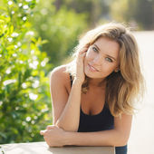 Portrait of a young beautiful smiling blonde woman outdoors — Stock Photo