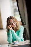 坐在一个咖啡馆与一杯咖啡一个可爱的金发微笑着女人的画像 — 图库照片