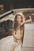 Beautiful young woman witting in a car on driver seat — Stock Photo