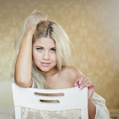 Portrait of young elegant woman sitting on chair in bedroom — Stockfoto