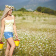 Attractive blonde in chamomile field. Young woman in wreath — Stock Photo #37562155