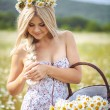 Attractive blonde in chamomile field. Young woman in wreath — Stock Photo #37562209