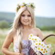 Attractive blonde in chamomile field. Young woman in wreath — Stock Photo #37562219