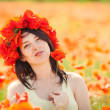 Pregnant happy woman in a flowering poppy field outdoors — Stock Photo #37567999