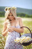 Attractive blonde in chamomile field. Young woman in wreath — Stock Photo