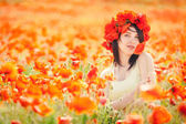 Pregnant happy woman in a flowering poppy field outdoors — Stock Photo