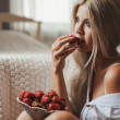 Young woman laying on bed with strawberry — Stock Photo #37571459