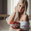 Young woman laying on bed with strawberry — Stock Photo #37571463