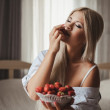 Young woman laying on bed with strawberry — Stock Photo #37571481
