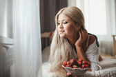 Young woman laying on bed with strawberry — Stock Photo