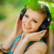 Beautiful young woman listen to music wearing headphones outdoor — Stock Photo #37638517