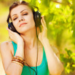 Beautiful young woman listen to music wearing headphones outdoor — Stock Photo #37638519