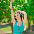 Beautiful young woman listen to music wearing headphones outdoor — Stock Photo #37638547