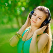 Beautiful young woman listen to music wearing headphones outdoor — Stock Photo #37638555