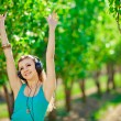 Beautiful young woman listen to music wearing headphones outdoor — Stock Photo #37638559
