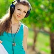 Beautiful young woman listen to music wearing headphones outdoor — Stock Photo