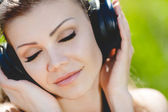 Beautiful young woman listen to music wearing headphones outdoors — ストック写真
