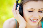 Beautiful young woman listen to music wearing headphones outdoors — Stock Photo