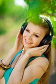 Beautiful young woman listen to music wearing headphones outdoor — Stock Photo